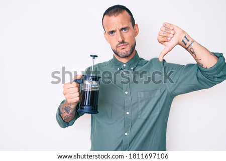 Young handsome man with tattoo holding french coffee maker with angry face, negative sign showing dislike with thumbs down, rejection concept