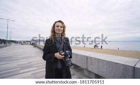 Woman photographer walks along embankment. Action. Woman takes pictures of embankment with seascape on camera. Woman on vacation takes picture of embankment on background sea in cloudy weather