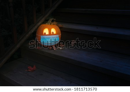 Lighted Carved Jack-o-Lantern dressed up for Halloweeen with COVID-19 Pandemic face mask Royalty-Free Stock Photo #1811713570