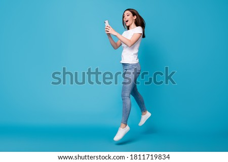 Full length body size view of her she attractive slim fit glad cheerful girl blogger jumping using cell app 5g fast speed dating service isolated bright vivid shine vibrant blue color background