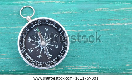 Classic round compass on green wooden vintage background as symbol of tourism with compass, travel with compass and outdoor activities with compass #1811759881