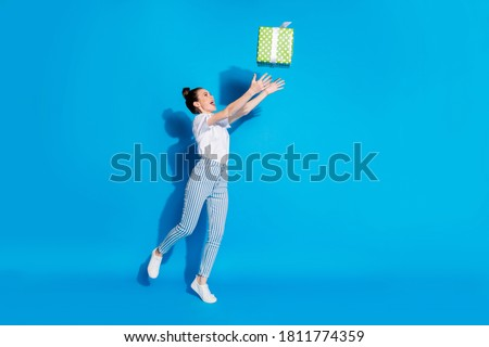 Full length photo of positive shocked girl catch air fly dream green big gift box she get receive 14-february 8-march wear white good look clothes sneakers isolated shine color background #1811774359