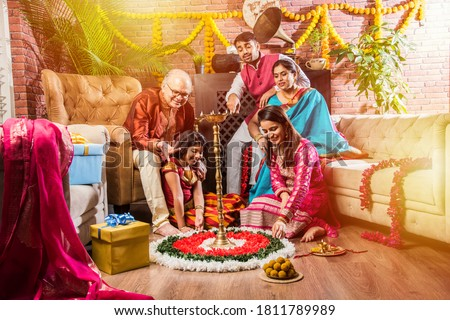 Happy Indian Family Celebrating Ganesh Festival or Chaturthi - Welcoming or performing Pooja and eating sweets in traditional wear at home decorated with Marigold Flowers Royalty-Free Stock Photo #1811789989