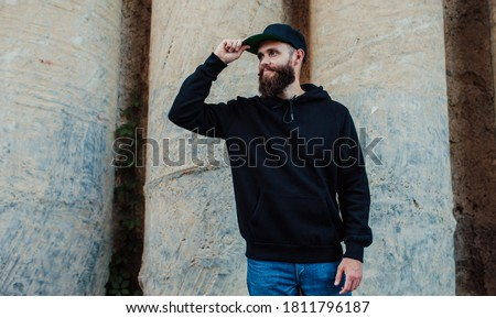 City portrait of handsome hipster guy with beard wearing black blank hoodie or sweatshirt with space for your logo or design. Mock up for print