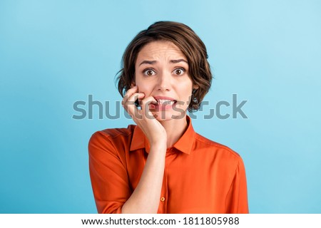 Oh no I failed again. Closeup photo of sad terrified lady horrified facial expression made big mistake feel guilty bite lips fingers wear orange shirt isolated blue color background #1811805988