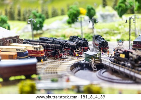 Train hobby model on the model railway. There are hundreds of metres of tracks, tens of models of trains or models of cars that give each other way at crossing. Royalty-Free Stock Photo #1811814139