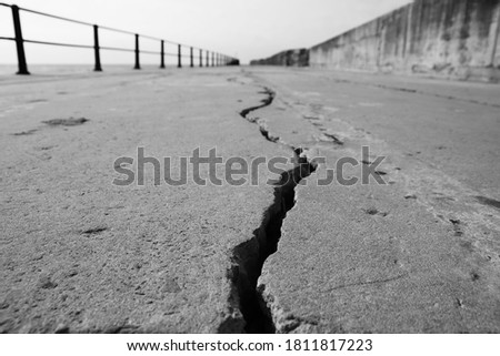 A large crack in concrete. Earthquake concept photo. This picture has selective focus.  Royalty-Free Stock Photo #1811817223