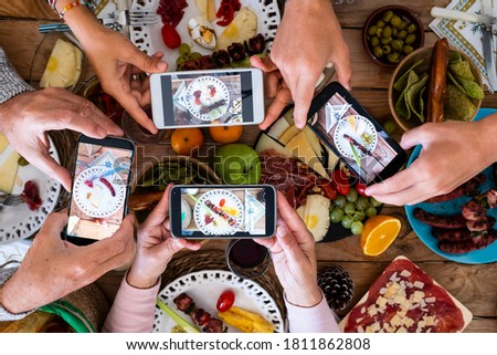 People eating together taking food picture with smartphone to share on social media - concept of celebration - wooden table and mixed food in background