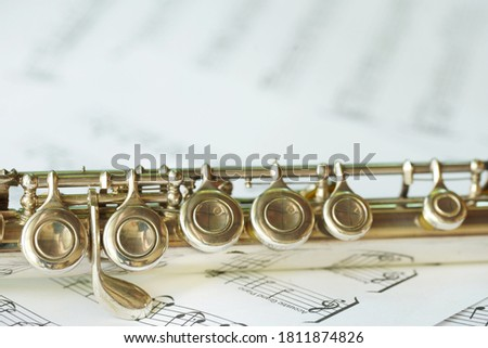 Flute, woodwind brass instrument in classical orchestra. Silver modern flute on white sheet music note for education and performance. Song composer on paper with instrument. Royalty-Free Stock Photo #1811874826