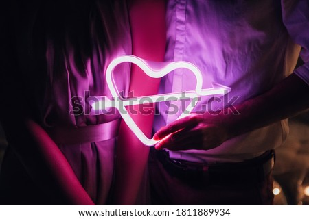 Glowing bright luminous neon heart sign pierced by cupid arrow, amour shape in vivid colors. Newlyweds holding digital shiny love target. Lovely young couple have a date, spending time together. #1811889934