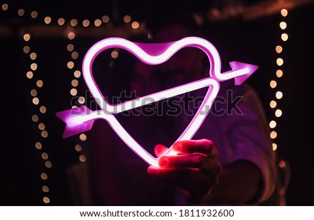 Glowing bright luminous neon heart sign pierced by cupid arrow, amour shape in vivid colors. Newlyweds holding digital shiny love target. Lovely young couple have a date, spending time together. #1811932600