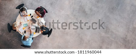 Top view of university students sitting at a table studying and working on laptop Royalty-Free Stock Photo #1811960044