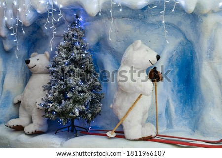 A huge toy polar bear sits on skis, and there is snow all around. Christmas card with a picture of a Christmas tree and a bear on skis.