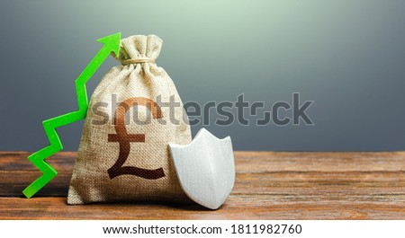 British pound sterling money bag with a shield and a green arrow up. Increasing maximum amount of guaranteed deposits insurance compensation. Safety security of investments, financial system stability #1811982760