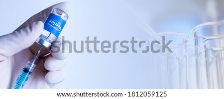Suspended Covid-19 vaccine test - Man withdrawing liquid with syringe from the Sars-Cov-2 Coronavirus Vaccine vial - Test tubes at the bottom of the image - Space for text #1812059125