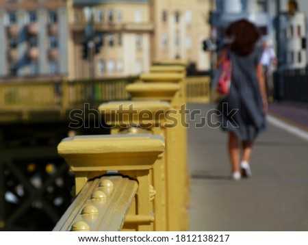 Yellow painted cast iron bridge railing in diminishing perspective. woman pedestrian walking by. light gray asphalt sidewalk. summer scene. colorful stucco facades in the background. travel concet #1812138217