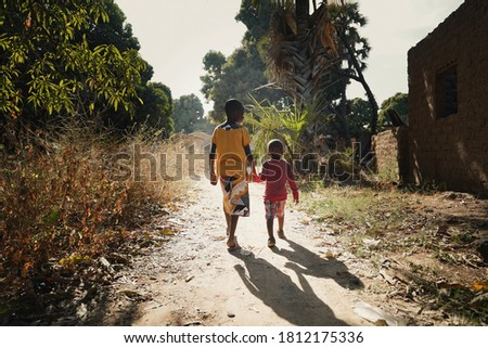 Sunset Picture of African Boys Brothers Walking Outdoors in a Typical Landscape
