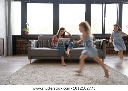 Young single mother working on laptop in loft sitting on couch while her daughters running around her and shouting. Royalty-Free Stock Photo #1812182773