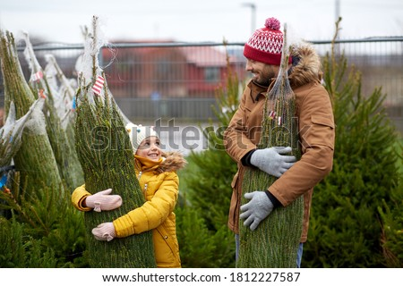 family, winter holidays and people concept - happy father and little daughter buying christmas tree at street market Royalty-Free Stock Photo #1812227587