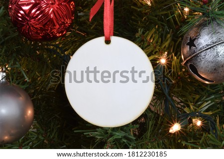 Blank Round Christmas Ornament hanging from a lit up Christmas tree surrounded by ornaments.  Royalty-Free Stock Photo #1812230185