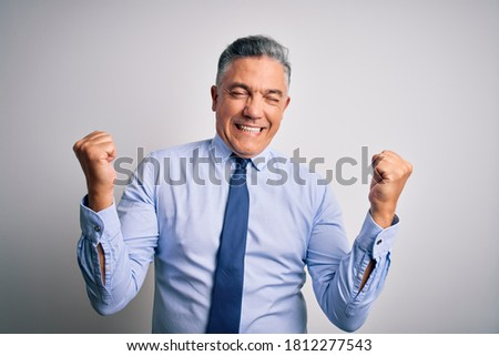 Middle age handsome grey-haired business man wearing elegant shirt and tie very happy and excited doing winner gesture with arms raised, smiling and screaming for success. Celebration concept.