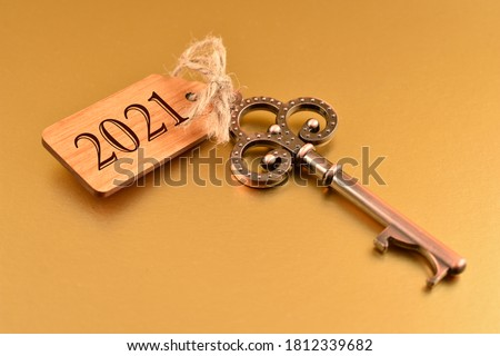 2021 New Year Key stock images. Old decorativekey with wooden tag 2021 isolated on a golden background. Golden New Year 2021. Key with number 2021 stock images Royalty-Free Stock Photo #1812339682