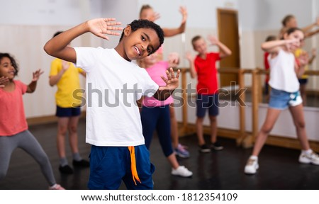 Portrait of smiling african boy showing dance elements during group class in dance center Royalty-Free Stock Photo #1812354109
