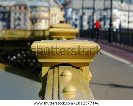 Yellow cast iron bridge railing in diminishing perspective with red cyclist passing by. selective focus. light gray asphalt sidewalk. summer scene. blurred colorful stucco facades in the background. #1812377146