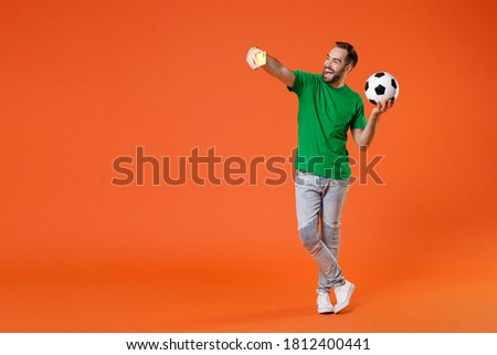 Full length portrait funny man football fan in basic green t-shirt support favorite team with soccer ball doing selfie shot on mobile phone isolated on orange background. People sport leisure concept