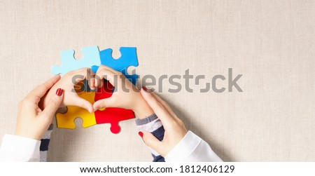 World autism awareness day, understanding & love concept, a beautiful mother holding hands of little autistic child making heart shape over symbol colored puzzle. ASD, April 2, Top view banner.
