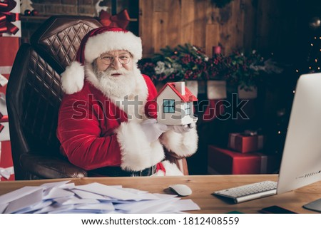 Happy x-mas christmas season shopping sales. Jolly white grey beard hair santa claus sit table hold small insurance building wear cap in house indoors with spirit atmosphere advent tinsels #1812408559
