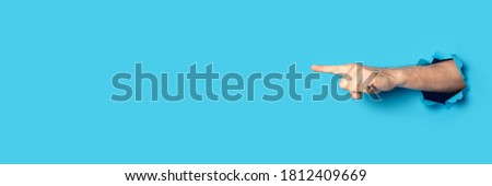 Hand points to something on a blue background. Gesture look at this, pay attention Royalty-Free Stock Photo #1812409669