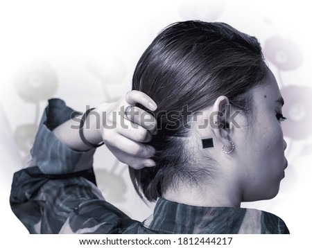 A small microchip implanted at the back of the ear of a woman. Concept of Computer enhanced human or cyborg. Isolated on white background.