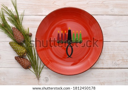 Kwanzaa Kinara Red Plate on whitewashed wood with pine cones and evergreen branch