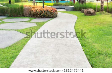 Walkway and bush. That is concrete pavement, floor, passage, path, footpath, pathway or passageway with nature for walking along and connecting different section of a building, park or garden. Royalty-Free Stock Photo #1812472441