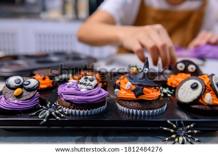 Cooking delicious homemade cake and decorate cupcake for Halloween festive. Preparing and mixing ingredients for sweet food dessert in kitchen at home. #1812484276