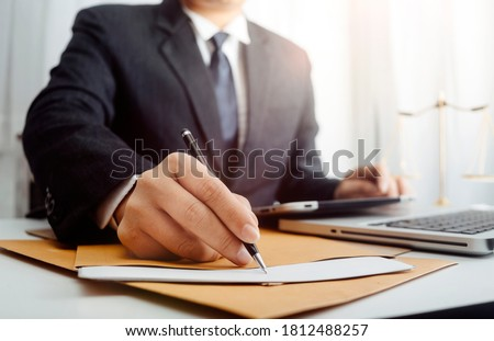 Justice and law concept.Male judge in a courtroom with the gavel, working with, computer and docking keyboard, eyeglasses, on table in morning light Royalty-Free Stock Photo #1812488257
