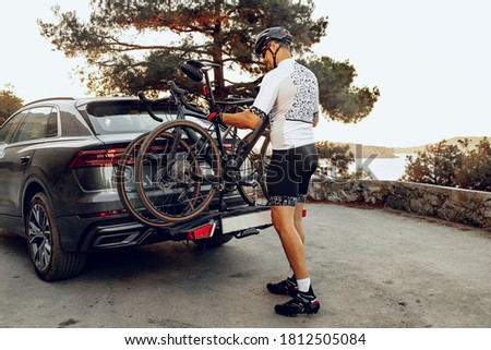 Male cyclist loading his bicycle on a rack of his crossover car Royalty-Free Stock Photo #1812505084