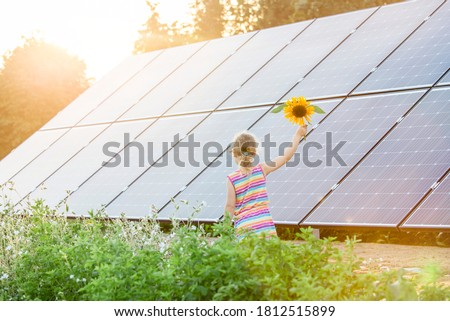 Young 6 year old blonde girl child standing in front of small solar panel farm in countryside. Renewable energy concept. Sun lens flare. Royalty-Free Stock Photo #1812515899