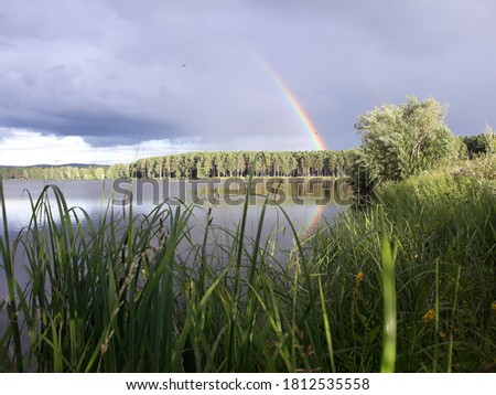 pictured is a rainbow over a lake in a thunderstorm