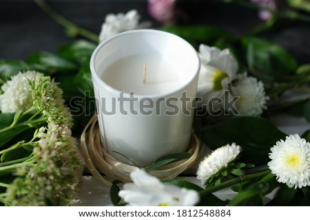 white scented candle and delicate flowers. home fragrances for relaxation and calm. flower fragrance for home. unbranded ceramic candle. #1812548884