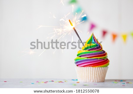 Colorful rainbow cupcake with celebration sparkler Royalty-Free Stock Photo #1812550078