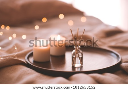 Aroma bamboo sticks in bottle with scented liquid with candles staying on wooden tray in bed closeup.  Royalty-Free Stock Photo #1812653152