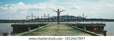 Woman standing on a wooden jetty  enjoying the sunshine with arms up. Woman on a pier on the lake greeting the sun with arms wide open. Authentic image, cinematic analog film look. Banner wide format. Royalty-Free Stock Photo #1812667897