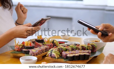 Two people taking pictures of their colorful vegan sushi sets with smartphones during lunch. Healthy vegan lifestyle concept