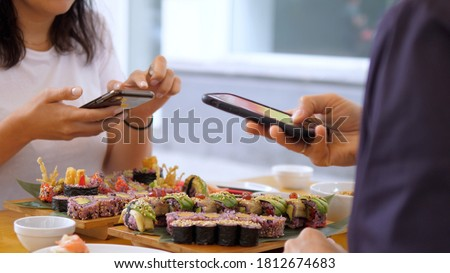 Food blogging. Girls taking pictures of their sushi at lunch. Artisan Japanese cuisine