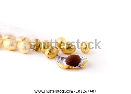 Cellophane bag of gold coloured chocolate mini easter eggs, lying down on a white surface with a couple of the eggs out of the bag. Focus is on the front egg which unwrapped. #181267487