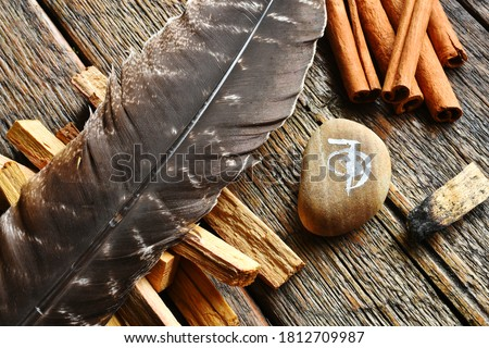 A top view image of a brown feather with various smudge sticks and reiki healing symbol.  Royalty-Free Stock Photo #1812709987