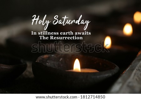 Holly week concept with candle and inspirational quote - Holy Saturday. In stillness earth awaits The Resurrection. On dark background of burning candles in traditional bowl ceramic in the church. Royalty-Free Stock Photo #1812714850