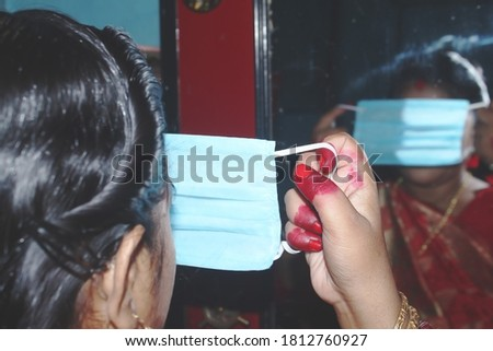 Safety first>>>>Housewife getting ready in front of mirror by adjusting medical mask before going out during festival celebration.